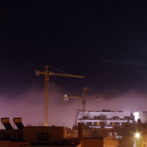 Construction cranes rising through the mist
